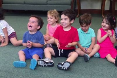 Little Boy Can't Resist Laughing While Teacher Sings A Song